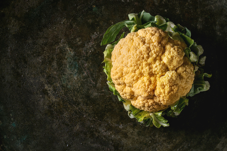 Fresh raw yellow organic cauliflower, cabbage romanesco over dark texture background. Top view with space. Healthy eating concept Imagens