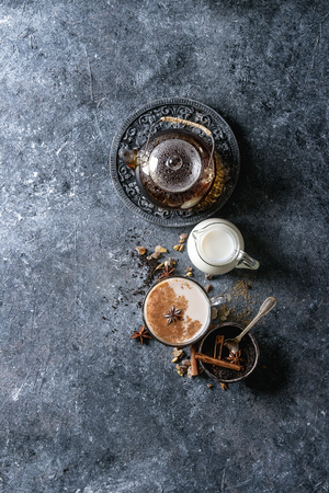 Glass cup of traditional indian masala chai tea with ingredients above. Cinnamon, cardamom, anise, sugar, black tea in glass teapot, jug of milk over dark texture background. Top view with copy space