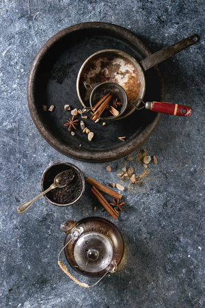 Vintage pot of traditional indian masala chai tea with ingredients above. Cinnamon, cardamom, anise, sugar, black tea in glass teapot over dark texture background. Top view with space Stock fotó
