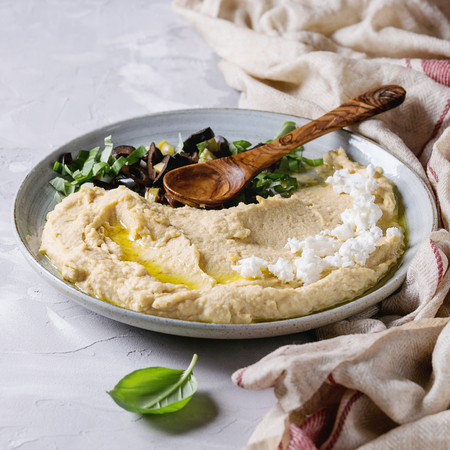 Homemade traditional spread hummus with chopping olives, oil and herbs on blue plate, served with feta cheese, spoon, basil, textile on gray texture background. Mediterranean snack. Square image Stock Photo