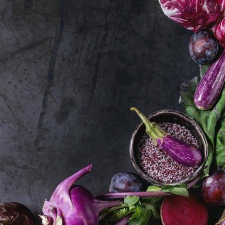 Assortment raw organic of purple vegetables mini eggplants, spring onion, beetroot, radicchio salad, plums, kohlrabi, flower salt over dark metal background. Top view with space. Food frame. Square image