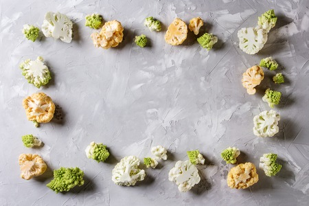 Variety of fresh raw organic colorful cauliflower and cabbage romanesco over gray texture surface. Food frame background. Top view with space. Healthy eating concept