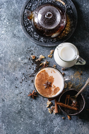 Glass cup of traditional indian masala chai tea with ingredients above. Cinnamon, cardamom, anise, sugar, black tea in glass teapot, jug of milk over dark texture background. Top view with space