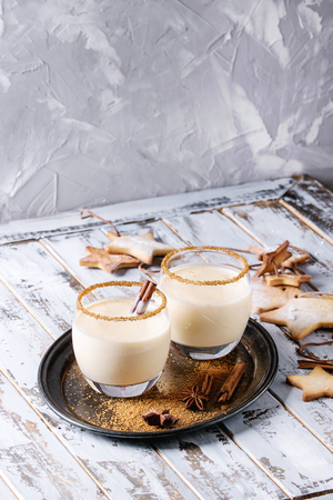 Eggnog Christmas milk cocktail with cinnamon, served in two glasses on vintage tray with shortbread star shape sugar cookies different size over white wooden plank table.
