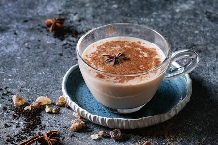 青いソーサーは上記の食材の伝統的なインドのマサラ チャイのグラス。シナモン、カルダモン、アニス、砂糖、紅茶濃いテクスチャ背景の上。スペ
