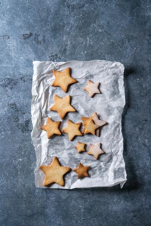自家製ショートブレッドスター形状砂糖クッキーは、青色のテクスチャの背景上にベーキングペーパー上の糖粉と異なるサイズ。クリスマスの御馳 写真素材