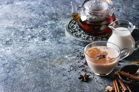 Glass cup of traditional indian masala chai tea with ingredients above. Cinnamon, cardamom, anise, sugar, black tea in glass teapot, jug of milk over dark texture background with copy space Stock Photo