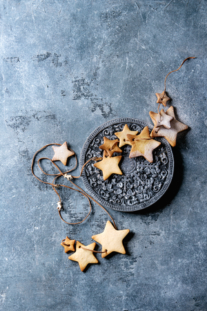 Homemade shortbread star shape sugar cookies different size with sugar powder on thread with wood ornate board over blue texture surface. Christmas treat background. Top view with space