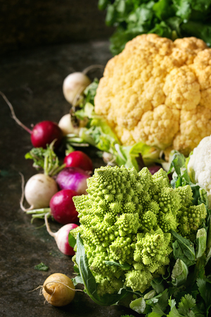 Variety of fresh raw organic colorful cauliflower, cabbage romanesco and radish with bundle of coriander over dark texture background. Close up. Healthy eating concept