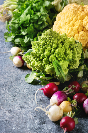 Variety of fresh raw organic colorful cauliflower, cabbage romanesco and radish with bundle of coriander over dark texture background. Close up with space. Healthy eating concept Imagens