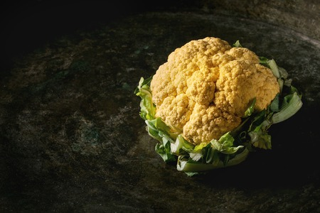 Fresh raw yellow organic cauliflower, cabbage romanesco over dark texture background. Healthy eating concept