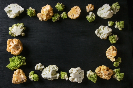 Variety of fresh raw organic colorful cauliflower and cabbage romanesco over black wooden surface. Food frame background. Top view with space. Healthy eating concept