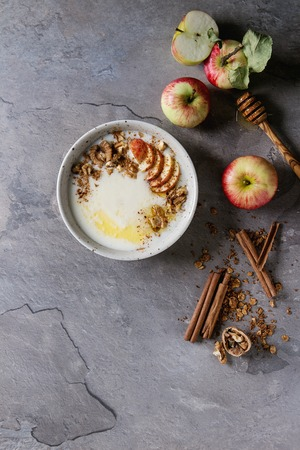 Bowl of milk cereal porridge with additives and butter, served with apples and cinnamon over gray kitchen table. Top view with space