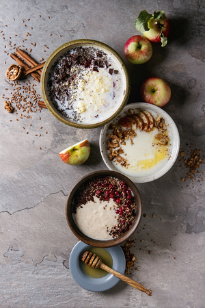 Variety bowls of milk cereal porridge with different additives, served with apples, berries and seeds over gray kitchen table. Top view with space Stock Photo