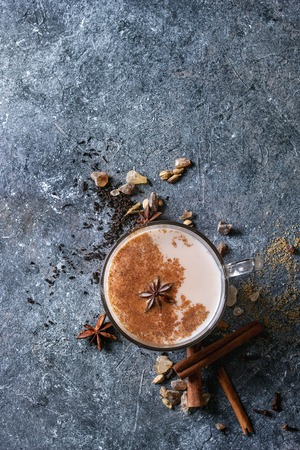 Glass cup of traditional indian masala chai tea with ingredients above. Cinnamon, cardamom, anise, sugar, black tea over dark texture background. Top view with copy space Stock Photo