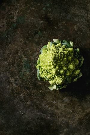 Fresh raw organic cabbage romanesco over dark texture background. Top view with space. Healthy eating concept Imagens