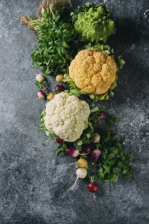 Variety of fresh raw organic colorful cauliflower, cabbage romanesco and radish with bundle of coriander over dark texture background. Top view with space. Healthy eating concept Imagens