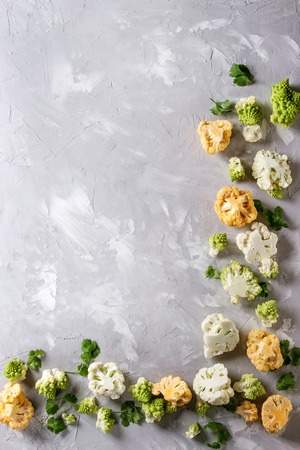 Variety of fresh raw organic colorful cauliflower, cabbage romanesco and coriander leaves over gray texture surface. Food frame background. Top view with space. Healthy eating concept