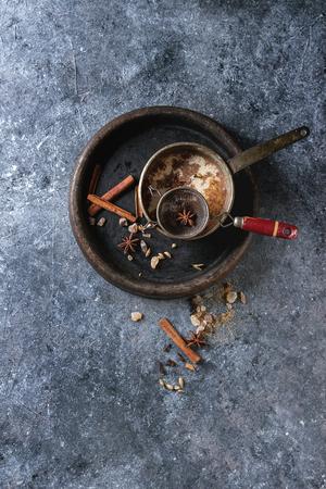 Pote del vintage del té indio tradicional del chai del masala con los ingredientes arriba. Canela, cardamomo, anís, azúcar en la bandeja de piedra sobre fondo oscuro de la textura. Vista superior con espacio de copia Foto de archivo - 88365577