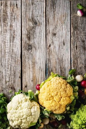 Variety of fresh raw organic colorful cauliflower, cabbage romanesco and radish with bundle of coriander over old wooden background. Top view with copy space. Food farm market concept