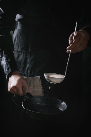 Mensenchef-kok in zwart schort gietend deeg van gietlepel voor het koken van pannekoeken in gietijzerpan. Donkere rustieke stijl.
