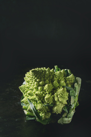 Fresh raw organic cabbage romanesco over dark texture background. Healthy eating concept