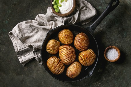 Accordion hasselback baked potatoes served in cast-iron pan with sea salt, cream-fresh and green spring onion on textile napkin over old dark metal background. Top view, space. Rustic style