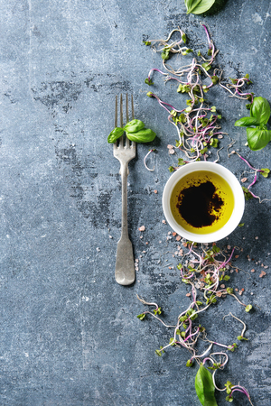 Young radish sprouts with pink himalayan salt and basil leaves with bowl of olive oil and balsamic vinegar over blue texture background. Top view with copy space. Healthy diet concept, food background Stock Photo