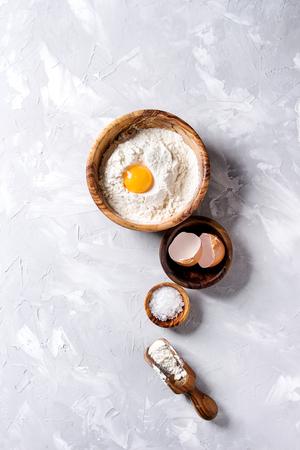 オリーブの木は、灰色のテクスチャの背景の上海の塩、小麦粉、全卵卵黄をボウルします。コピー スペース平面図です。コンセプトを焼く 写真素材