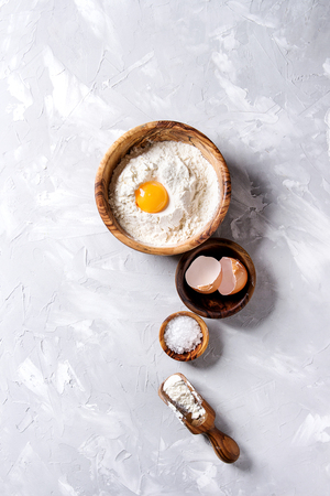Olive wood bowls with sea salt, wheat flour and whole egg yolk over gray texture background. Top view with copy space. Baking concept