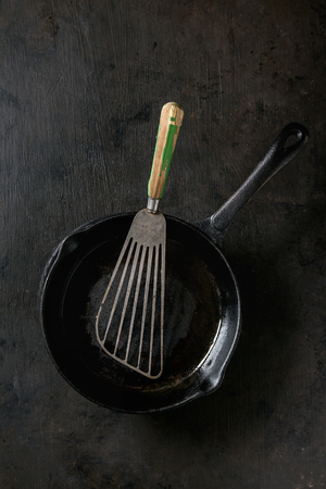 Empty oil cast-iron pan for cooking pancakes with vintage shovel over dark background. Cooking concept Reklamní fotografie