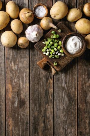 夕食のための原料。生全体洗浄有機ジャガイモ、タマネギ、ニンニク、塩、ネギとクリームの新鮮な古い木の板の背景の上のまな板の上です。スペ