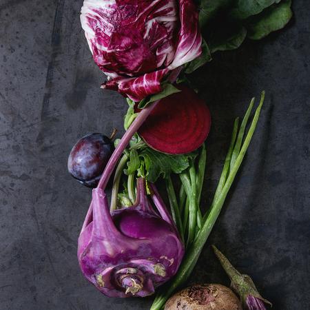 Assortment raw organic of purple vegetables mini eggplants, spring onion, beetroot, radicchio salad, plums, kohlrabi, flower salt over dark metal background. Top view with space. Square image