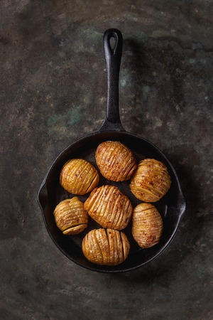 Accordion hasselback baked potatoes served in cast-iron pan over old dark metal background. Top view, space. Rustic style Stock Photo