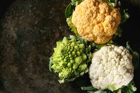 Variety of fresh raw organic colorful cauliflower and cabbage romanesco over dark texture background. Top view with space. Healthy eating concept Imagens