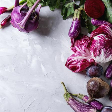 Assortment raw organic of purple vegetables mini eggplants, spring onion, beetroot, radicchio salad, plums, kohlrabi, flower salt over gray concrete background. Top view, space. Food frame. Square image