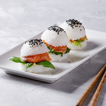 Mini rice sushi burgers with smoked salmon, green salad and sauces, black sesame served on white square plate with wooden chopsticks over gray concrete background. Modern healthy food. Square image Stock Photo