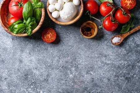 イタリアのカプレーゼ サラダの材料。モッツァレラチーズのボール、バッファロー、トマト、バジルの葉、酢、灰色のテクスチャ背景にオリーブの