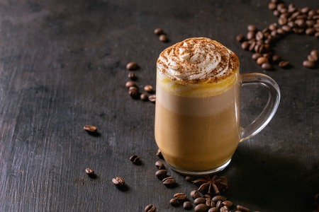Glass of spicy pumpkin latte with whipped cream and cinnamon standing on black serving board. Coffee beans and spices above. Dark background.