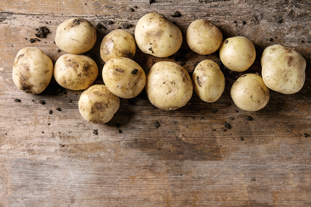 Raw whole organic potatoes with soil over old wooden background. Top view with copy space