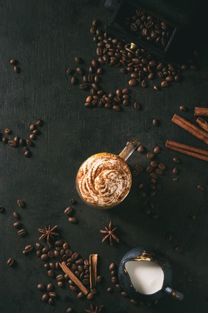 Glass of spicy pumpkin latte with whipped cream and cinnamon standing on black serving board. Coffee beans and spices above. Dark background. Top view, space.