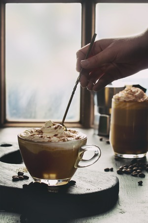 Glass of spicy pumpkin latte with whipped cream and cinnamon standing wooden serving board on cafe table near window with coffeepot and coffee beans above. Man hand taking cream by spoon.