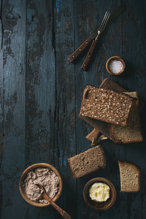Variety loaves of sliced homemade rye bread whole grain and seeds for breakfast with olive wood bowls of butter, salt, liver paste over old dark wooden background. Top view, space. Toned image