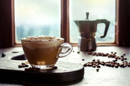 Glas van kruidige pompoen latte met slagroom en kaneel die houten dienende raad op koffielijst dichtbij venster met hierboven koffiekan en koffiebonen bevinden zich. Sfeervol ontbijt