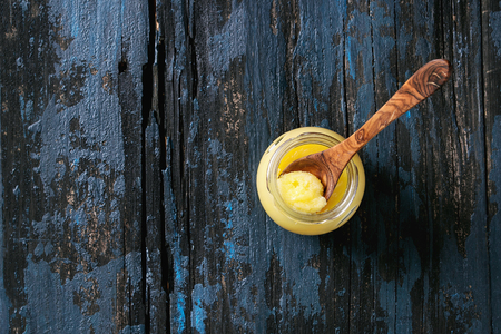 Glass of drawn ghee butter standing with wood spoon over old dark blue wooden background. Healthy eating. Top view, copy space Stok Fotoğraf