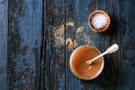 Słoik z domowym solonym sosem karmelowym z łyżeczką, brązowym cukrem i miską soli. Na starym ciemnym niebieskim tle drewnianych. Widok z góry z przestrzenią