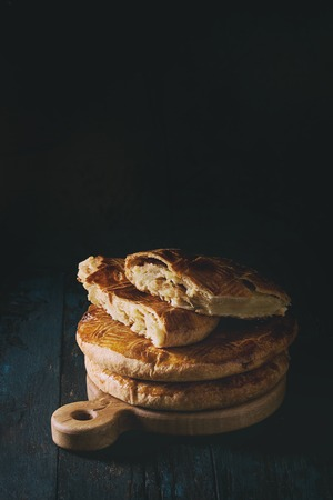 Traditional country sweet homemade armenian cake gata. whole and sliced cakes in stack on wooden serving board over old dark wooden table. Close up with space. Toned image