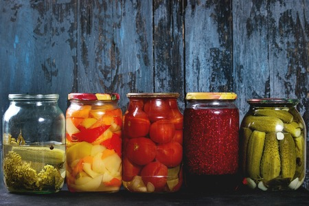 Variety glass jars of homemade pickled or fermented vegetables and jams in row with old dark blue wooden plank background. Seasonal preserves. Stock Photo