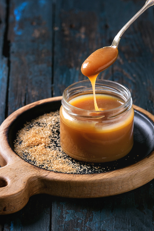 Glass jar of homemade salted caramel sauce on wooden serving board with ingredients brown sugar above. Caramel flowing from spoon. Over old dark blue wooden background.
