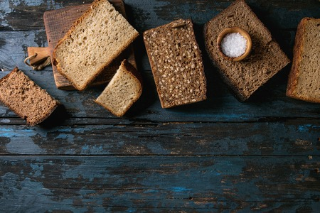 Variety loaves of sliced homemade rye bread whole grain and seeds on wooden cutting board with bowl of salt over old dark wooden background. Top view, copy space. Healthy eating